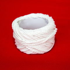 Roll of white string on a red fabric.