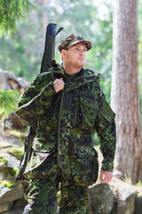 young soldier or hunter with gun in forest