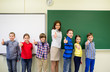 group of school kids and teacher showing thumbs up