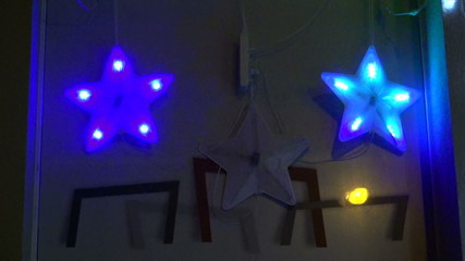 blinking three Christmas star decorations on house wall