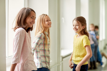group of smiling school kids in corridor