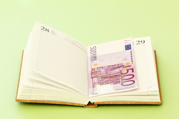 Blank page of note book and five hundred euro banknote
