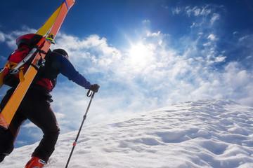 Ski mountaineer walking up along a steep snowy ridge