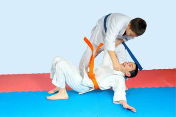 Boy with blue belt is the throwing athlete with an orange belt