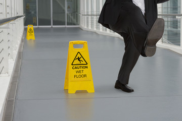 Man in suit slipping on wet floor