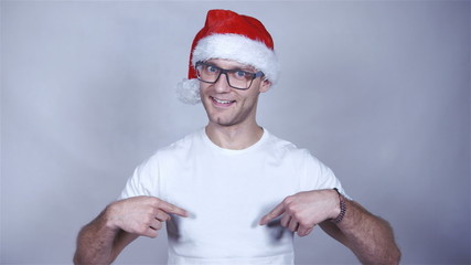 Handsome christmas man is posing in studio, pointing himself.