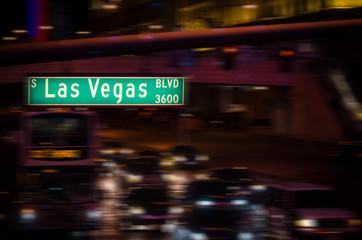 Las Vegas Boulevard street sign at night with motion traffic.