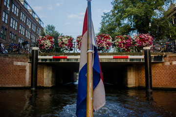 View of Netherlands Flag on back of Canal
