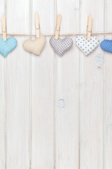 Valentines day toy hearts hanging on rope over white wooden back