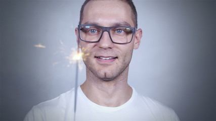 Smart looking guy with sparkles smiling over grey background.