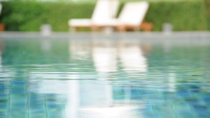 Water in swimming pool with beach chair background