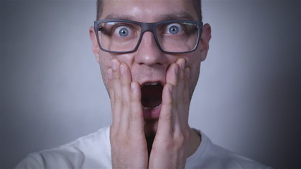 Portrait of amazed, scared man in studio. Close up.