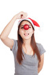Asian girl with red santa hat hold bauble at her nose