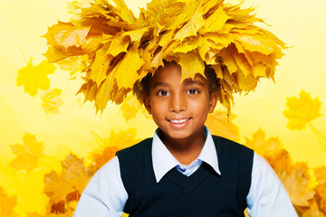 Smiling black boy wearing maple leaves crown