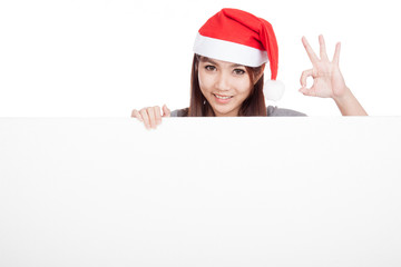 Asian girl with red santa hat show OK with a blank sign