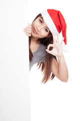Asian girl with santa hat peeking from behind a blank sign show