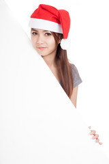 Asian girl with red santa hat with oblique blank sign