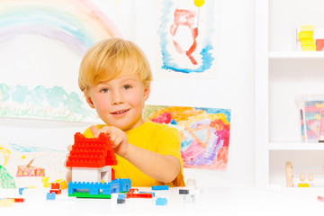 Handsome blond boy building house