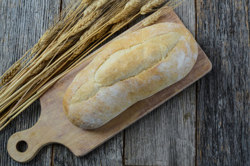 Bread and Wheat on a Rustic Cutting Board