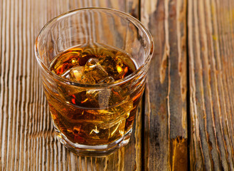 Glass of whiskey on  wooden background