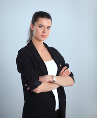 Young woman standing, isolated on gray background
