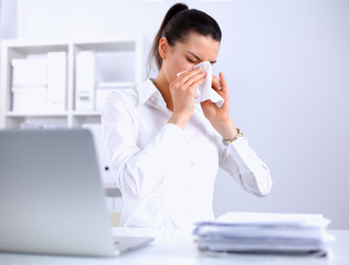 Young businesswoman blowing her nose, sits at the desk