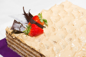Walnut layered cake with strawberry and chocolate garnish