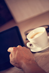Human Hand Using Digital Tablet And Cup Of Coffee Behind
