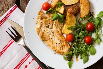 Slices of grilled chicken steak with potatoes and vegetables