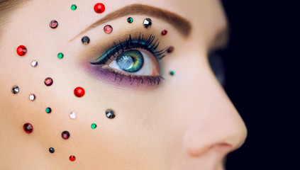 Arty make-up on woman eye with diamonds around. Perfect skin. Cl