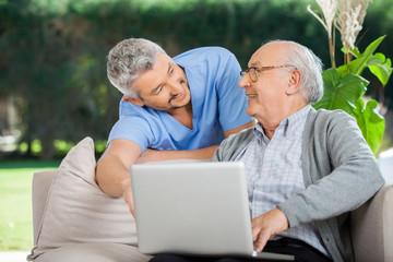 Smiling Nurse Assisting Senior Man In Using Laptop