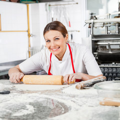 Happy Female Chef Rolling Pasta Sheet At Counter