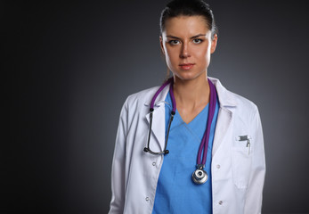 Young doctor woman with stethoscope isolated on grey