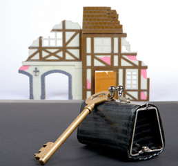 small purse with the key of the house in ruins