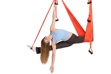 Young woman doing anti-gravity aerial yoga in hammock on a