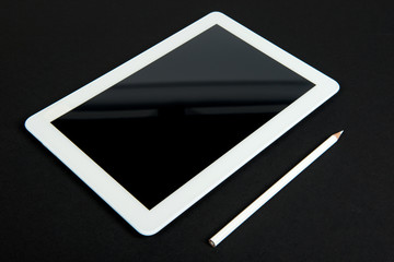 Touch pad with white pencil on black table