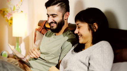 Couple smiling having fun with tablet in bed