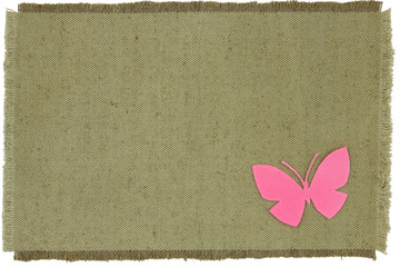 Homemade cardboard butterfly on green coarse cloth