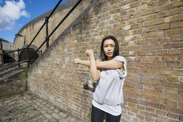 Beautiful fit woman exercising against brick wall