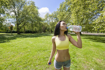 Fit young woman drinking water after jogging in park
