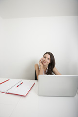 Beautiful businesswoman looking away while answering cell phone at desk in office