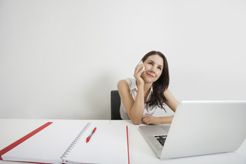 Smiling businesswoman looking away while answering cell phone at desk in office