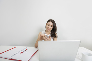 Young businesswoman using cell phone at desk in office
