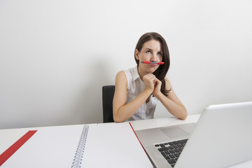 Thoughtful businesswoman holding pen under nose at desk in office
