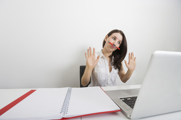 Astonished businesswoman looking at laptop while holding pen under nose in office