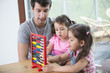 Father and daughters playing with abacus in house