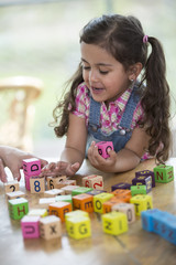 Happy girl playing with alphabet blocks at table