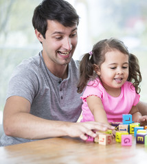 Happy father and daughter playing with building blocks at table in house