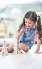 Little girl building blocks while sitting on hardwood floor