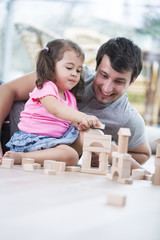 Little girl and father playing with wooden building blocks on floor